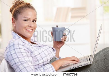 Young female working at home in bed, using laptop, drinking tea, coffee.
