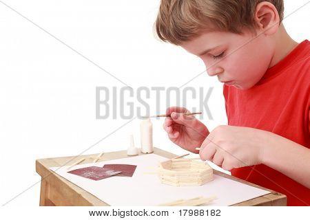kleiner Junge im roten T-shirt-Handwerk am kleinen Tisch, Kleber, Seitenansicht