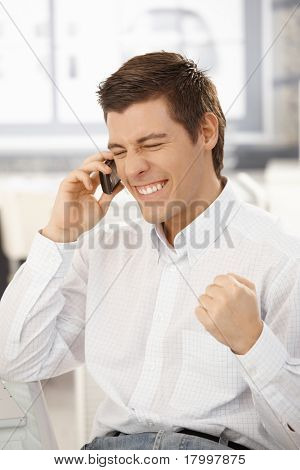 Businessman getting good news on mobile phone, happy about business success, raising fist, smiling with eyes closed.?
