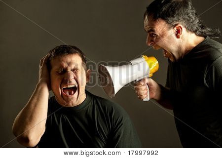 Infuriated man yelling with a megaphone at other man