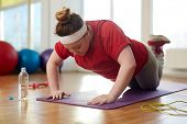 Portrait of young obese woman working out on yoga mat in sunlit fitness studio: performing knee push poster