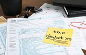 Paper sheet with text TAX DEDUCTIONS and individual tax return form on table poster