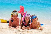 pic of children beach  - Children in snorkeling equipment lying on the beach and looking happy - JPG