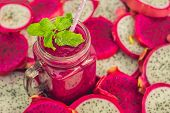 Smoothies Of Red Organic Dragon Fruit And Pieces Of Dragon Fruit On An Old Wooden Background poster