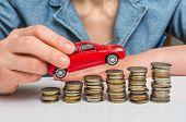 Businesswoman And Toy Car On Coin Stack poster