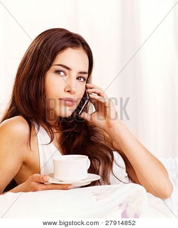 Woman Making Phone Call And Holding Cup Of Coffee In Bed