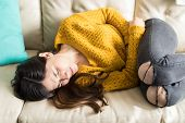 Young Woman In Sweater Feeling Intense Pain In Abdomen While Lying On Sofa poster