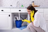 Sad Young Woman Calling Plumber In Front Of Water Leaking From Sink Pipe poster