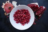 Hite Plate With Pomegranate Fruit Next To Pomegranate Pieces And Pomegranate Peel On A Dark Backgrou poster