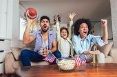 Happy African American Family Of Three Watching Tv And Cheering Sport Games On Sofa At Home poster