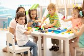Kindergarten Children Play Color Toys With Teacher In Playroom At Preschool. Education Concept. poster
