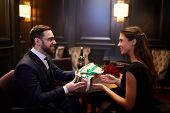 Happy young woman taking giftbox from hands of her boyfriend during romantic dinner in luxurious res poster