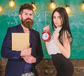 Discipline Concept. Man With Beard Hold Book And Sexy Girl Teacher Holds Alarm Clock, Chalkboard On  poster