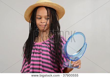 Young Black girl looking in mirror