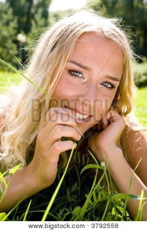 Young Blond Woman In A Park