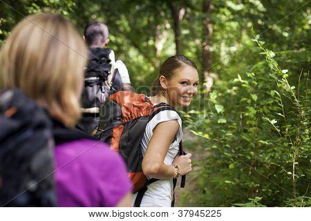 Pessoas com mochila fazendo Trekking em madeira