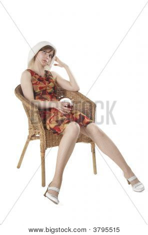 The Young As In Summer Dressed Girl Sits In Armchair With A Glass Of Wine And Thinks.
