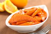 picture of batata  - Bowl of sweet potato wedges caramelized with brown sugar and fresh orange juice with a fork on the side and oranges in the back  - JPG