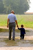 stock photo of holding hands  - Child walking hand in hand with his grandfather - JPG