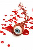 stock photo of gruesome  - A realistic looking eyeball in a pool of blood over a white background - JPG