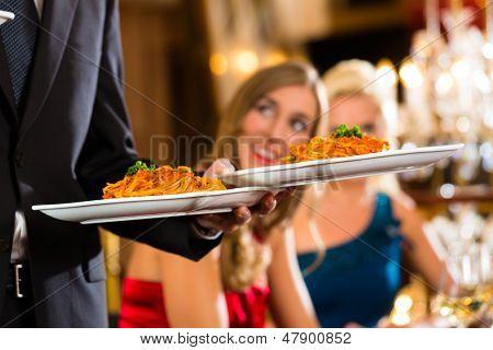 Buenos amigos para almorzar en un restaurante, el camarero sirve la cena