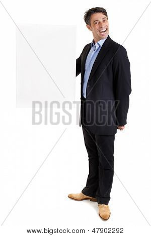 Dapper businessman with a cheesy grin holding up a rectangular blank white sign with copyspace for your text at arms length, isolated on white