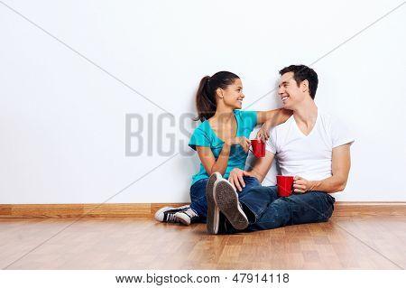 paar Umzug in leeren neuen Zuhause sitzen am Boden zusammen und Kaffee trinken