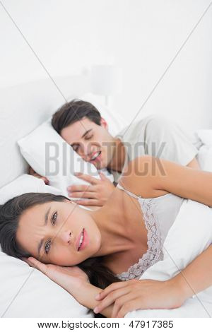 Pretty woman annoyed that her partner snoring in bed