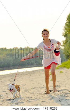 young girl and her amstaff dog running on beach
