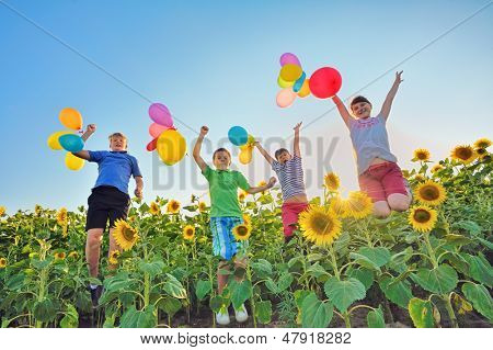 Jumping kids on field  in summer time