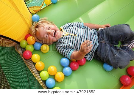2 year old boy smiling on an inflatable bouncy castle