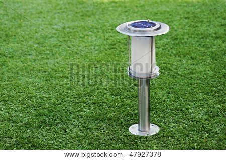 Solar-powered Lamp On Green Grass Background.