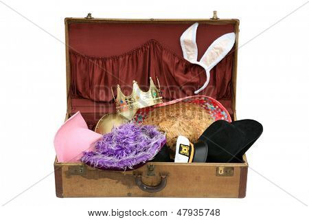 Old Vintage Suitcase Isolated on a white background, filled with funny hats and head wear. 1930's era suitcase with colorful hats and head wear from various parts of the world and styles. stock photo