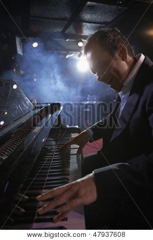Side view of a male pianist performing in jazz club