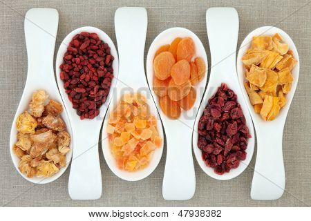 Dried fruit in white porcelain scoops over hessian background.