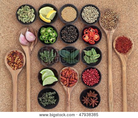 Large spice, herb and food ingredient selection in wooden bowls and spoons over cork background.