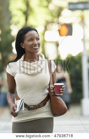 Happy African American businesswoman with newspaper and coffee cup walking on street