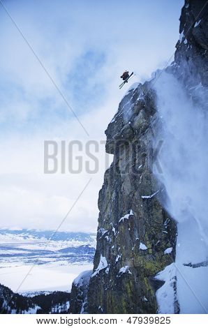 Low angle view of skier jumping from mountain cliff