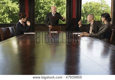 Multiethnic business people having discussion around boardroom table