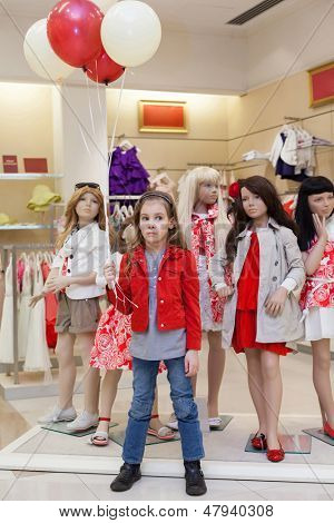 MOSCOW - MAR 18: Little Anya 7 years old with balloons stands with mannequins in the store children clothes Jakimanka on March 18, 2012 in Moscow, Russia.
