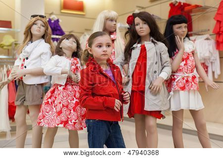 MOSCOW - MAR 18: Little Jeanette 6 years old trying on red clothes together with mannequins in the store childrens clothes Jakimanka on March 18, 2012 in Moscow, Russia.