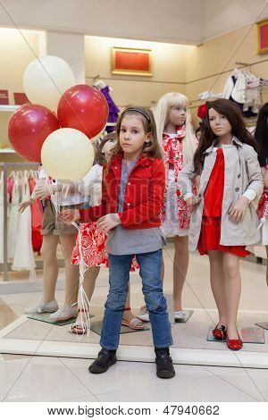 MOSCOW - MAR 18: Cute Anya 7 years old with balloons stands with mannequins in the store children clothes Jakimanka on March 18, 2012 in Moscow, Russia.