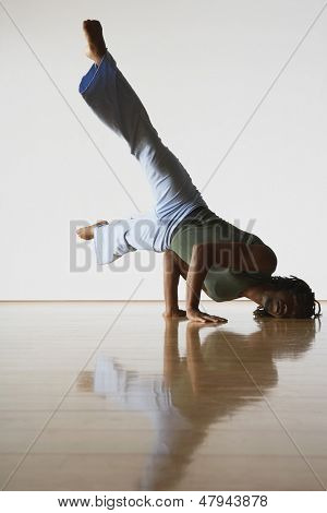Young male ballet dancer doing handstand in rehearsal room