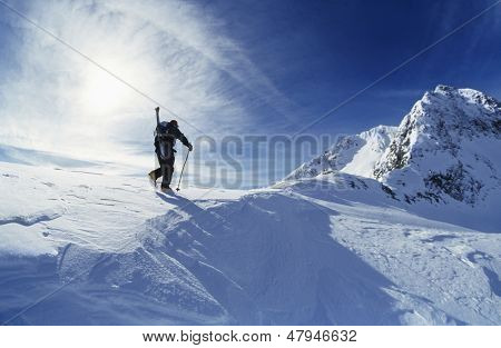 Rear view of skier hiking to mountain summit
