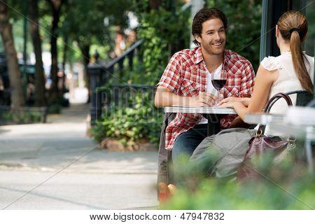 Couple drinking wine at sidewalk cafe