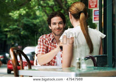 Couple sitting at sidewalk cafe