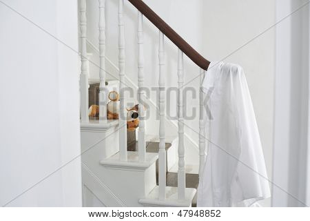 White shirt hanging on banisters with soft toy on steps