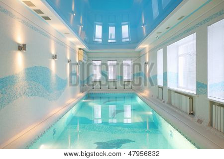 Beautiful pool with images of dolphins at bottom and clear water in big room.