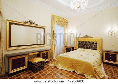 Bedroom with beautiful bed, bedside tables and big mirror in classic style.
