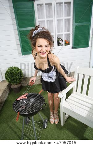 Junge schöne Hausmädchen Bratwurst auf Kohlenbecken in der Nähe von weißen Haus.